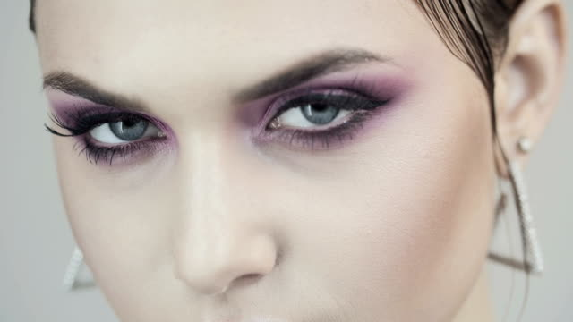face of a young beautiful girl with pink eyeshadows and pink lip gloss. - occhiata laterale video stock e b–roll