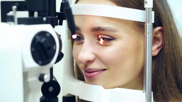 vidéos et rushes de visage d'une jeune femelle à un bureau d'ophtalmologiste. la femme de sourire retient les yeux ouverts pendant un examen optique. eye check up par microscope moderne. dispositif médical laser briller à l'intérieur de l'œil. - rétine