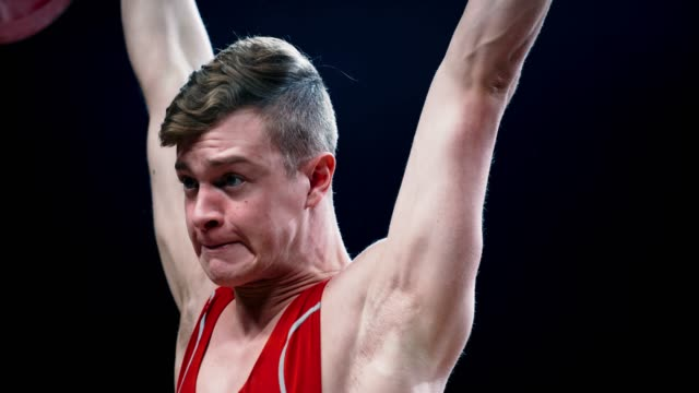 SLO MO Face of a young weightlifter as he raises the barbell above his head