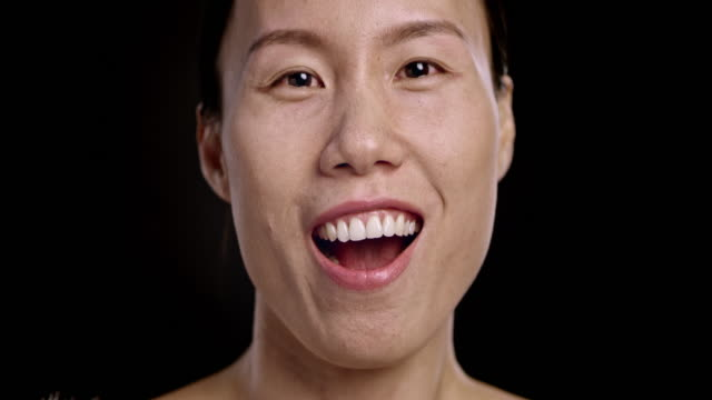 Face of an Asian woman laughing video