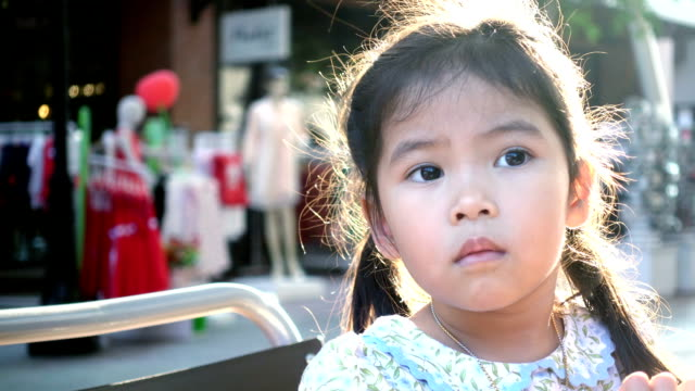 Face of asian little girl is looking doubt in downtown Video record with compact camera in light nature. expressionism stock videos & royalty-free footage