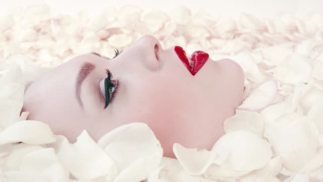 Face of beautiful girl in petals white roses. Face of beautiful girl in petals white roses. Advertising concept ofcosmetics for face based on herbs. Pure white skin on girl's face. Red bright lipstick on lips. Girl makes sigh, lies in rose petals skin care stock videos & royalty-free footage