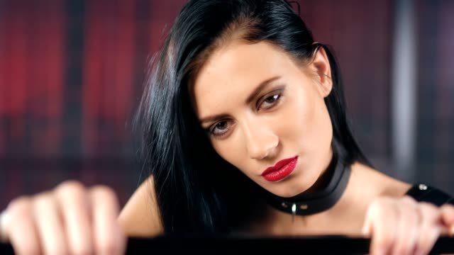 face of beautiful lust female in latex and leather collar having debauchery emotion - seduzione video stock e b–roll