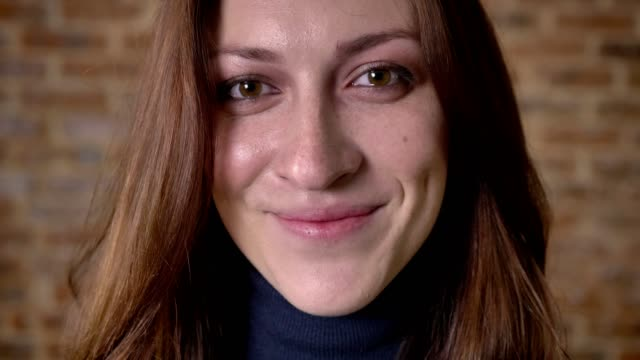 face of brown hair girl with eyes full of tears is watching at camera, blurred background - strillare video stock e b–roll