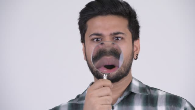 Face of funny young bearded Indian hipster man with magnifying glass