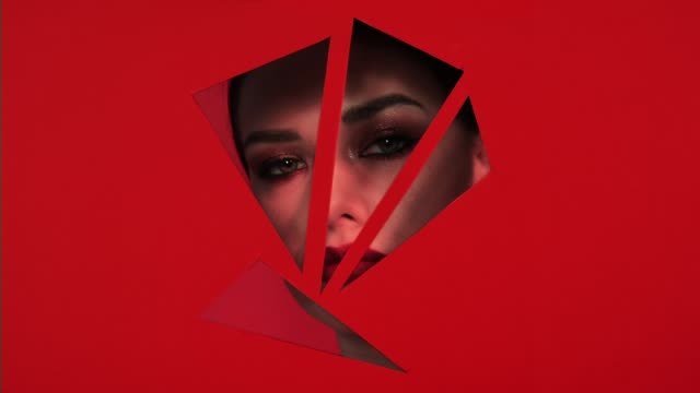 Face of girl  in holes of red background. Face of girl with beautiful bright make-up appears in holes of red paper background. Holes in the form of triangles. Mascara with sparkles and red lipstick. Advertising of female cosmetics. human lips stock videos & royalty-free footage
