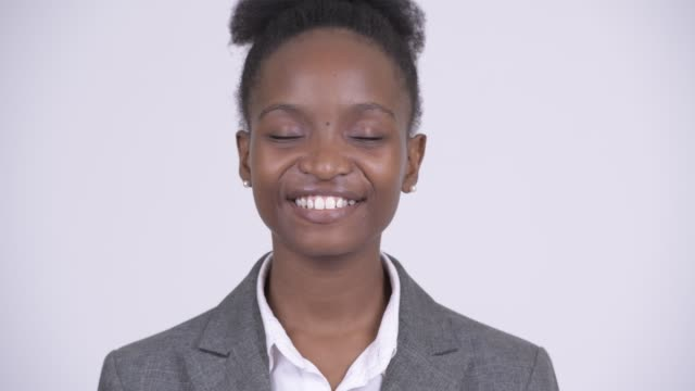 Face of happy young African businesswoman Studio shot of young beautiful African Zulu businesswoman with afro hair against white background eyes closed stock videos & royalty-free footage