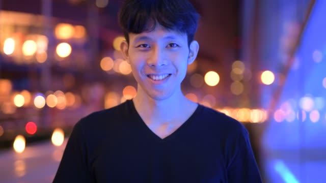 ansikte av lycklig ung asiatisk man leende i staden på natten - endast en man i 30 årsåldern bildbanksvideor och videomaterial från bakom kulisserna