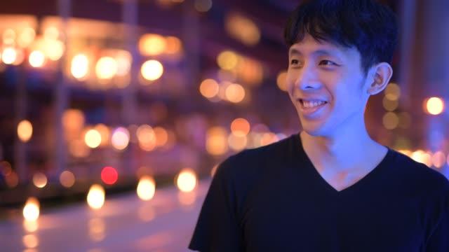 夜に屋外で考える幸せなアジアの若者の顔 - 人の居住地点の映像素材/bロール