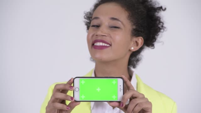 Face of happy young beautiful African businesswoman showing phone
