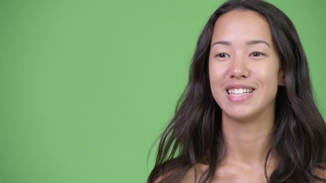 インタビューを受けている幸せな若い美しい多民族女性の顔 - スタジオ 日本人点の映像素材/bロール