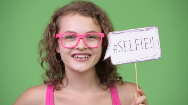 Face of happy young beautiful nerd woman with selfie paper sign Studio shot of young beautiful nerd woman with curly blond hair and blue eyes against chroma key with green background prop stock videos & royalty-free footage