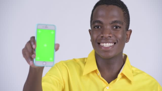 Face of happy young handsome African businessman showing phone