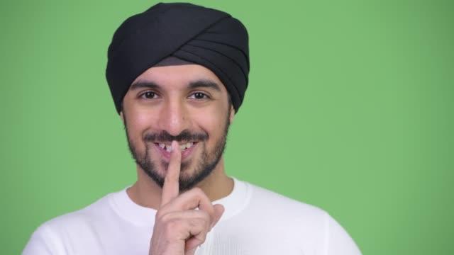 Face do homem indiano barbudo considerável novo feliz com o dedo nos bordos - vídeo
