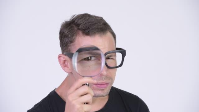 Face de eyeglasses desgastando do homem do lerdo e de usar a lupa - vídeo