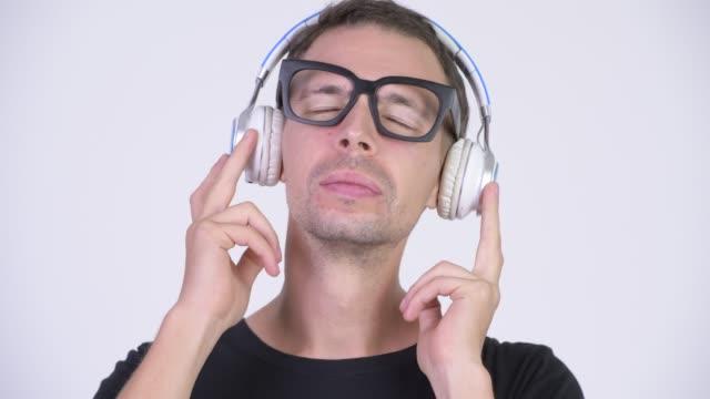Face do homem do lerdo com os eyeglasses que escutam a música - vídeo