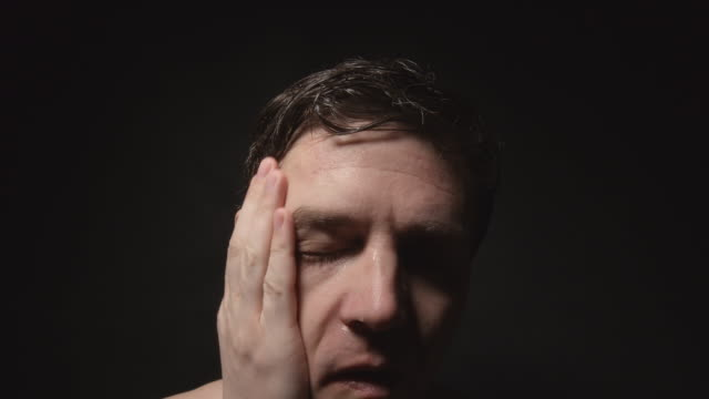 Face of sweating man wiped his wet forehead by hand in dark room video