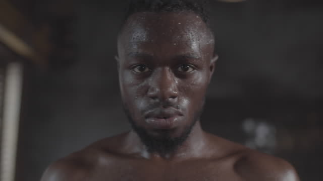 face of sweaty black boxer breathing heavily and staring at camera - guardare fisso video stock e b–roll