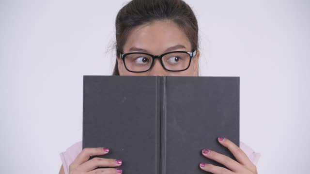 Face of young beautiful Asian businesswoman with book