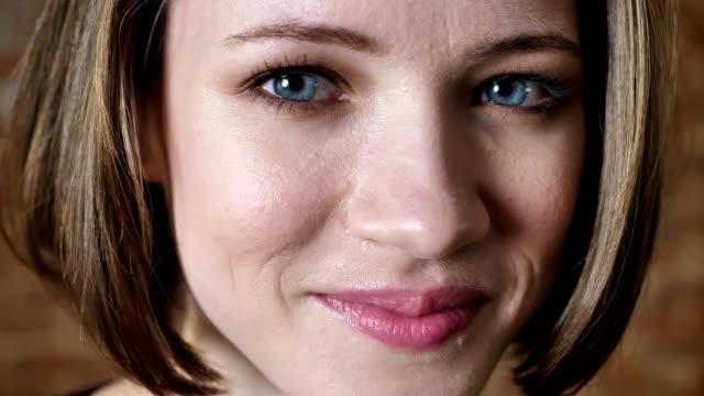 Cara de niña hermosa es sonriendo, mirando a cámara, Fondo de ladrillo - vídeo