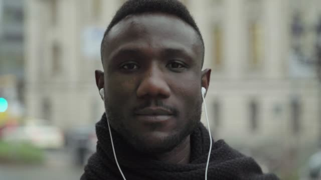 Face of Young Black Man with Earphones Looking at Camera