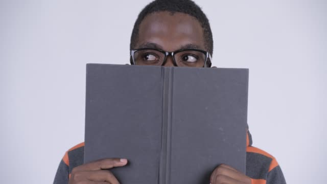 stockvideo's en b-roll-footage met gezicht van jonge knappe afrikaanse mens met boek - literatuur