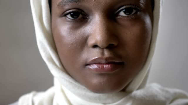 ansikte ofoung ledsen afrikanska muslimsk flicka i hijab är ser upp och titta på kameran, religioun koncept, grå bakgrund - hijab bildbanksvideor och videomaterial från bakom kulisserna