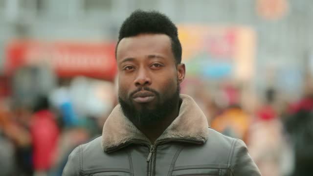 gesicht porträt ernstafrikanischen amerikanischen mann. afro schwarze menschen schauen kamera 4k. - starren stock-videos und b-roll-filmmaterial