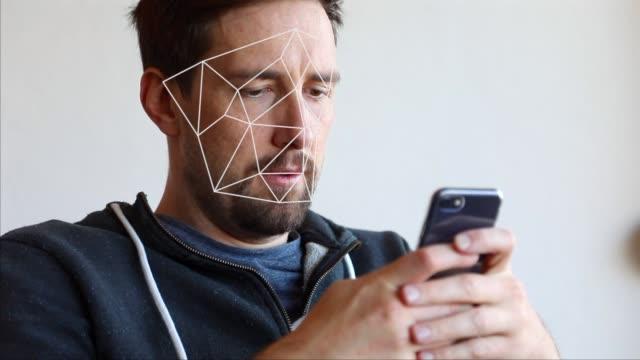 vídeos de stock e filmes b-roll de face recognition scanning with smartphone - documento