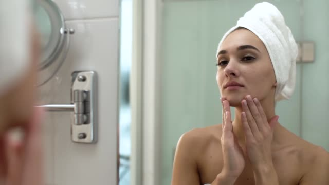 Face Skin Care. Woman Applying Cream On Skin At Bathroom Face Skin Care. Woman Applying Cream On Skin At Bathroom. Young Beautiful Female Wrapped In Towel After Shower indulgence stock videos & royalty-free footage
