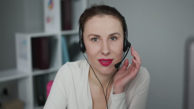 Face Young Female Woman Operator Look at Camera Smile in Call Center Office Business Worker Computer Corporate Headset Job Service Group Finance Sunshine Phone