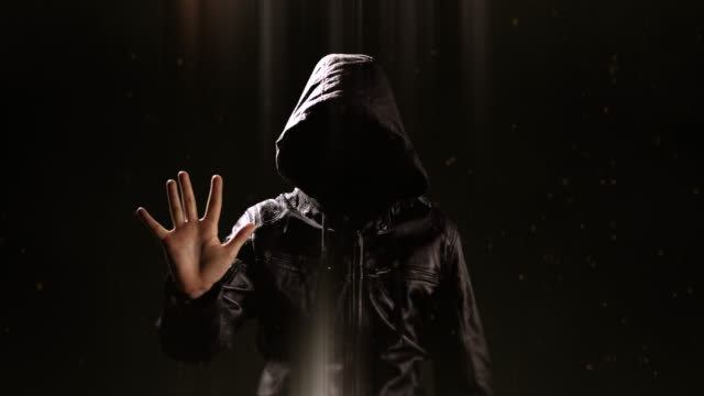 Faceless Hooded Man Silhouette with Hand Up, Black Background, Dark Criminal video