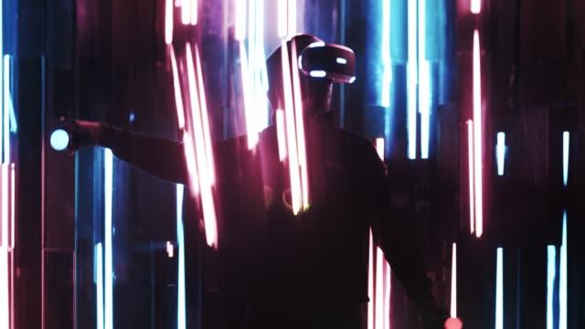 gesichtsloser mann in vr-headset spielt in dunklem innenraum - computerspieler stock-videos und b-roll-filmmaterial