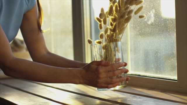 Faceless woman putting glass vase with dry flowers on windowsill