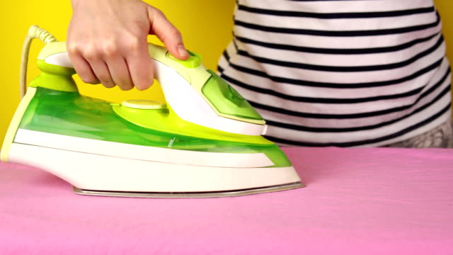 Faceless young woman irons bed linen on yellow background video
