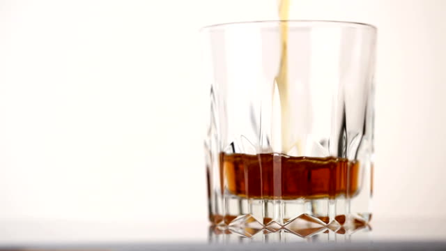Faceted glass filled with whiskey and ice cubes video
