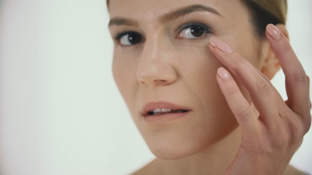 Facial Beauty. Middle Aged Woman Massaпing Skin Under Eyes