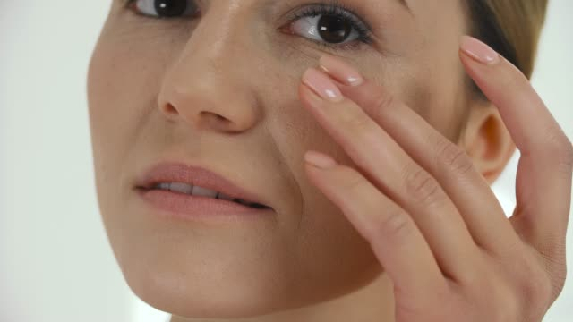 facial beauty. middle aged woman massaпing skin under eyes - морщинистый стоковые видео и кадры b-roll