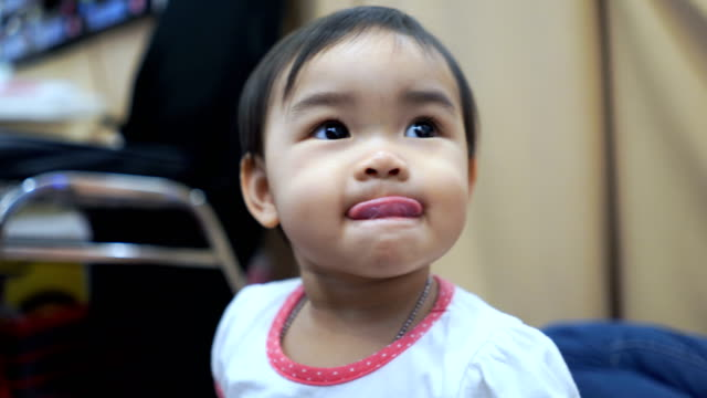facial expression by asian little girl , sticking out tongue - fare la lingua video stock e b–roll