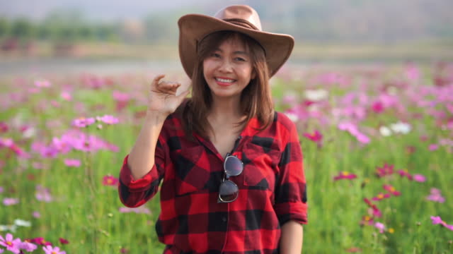 facial expression by Asian mature woman in cosmos meadow , beckoning sign
