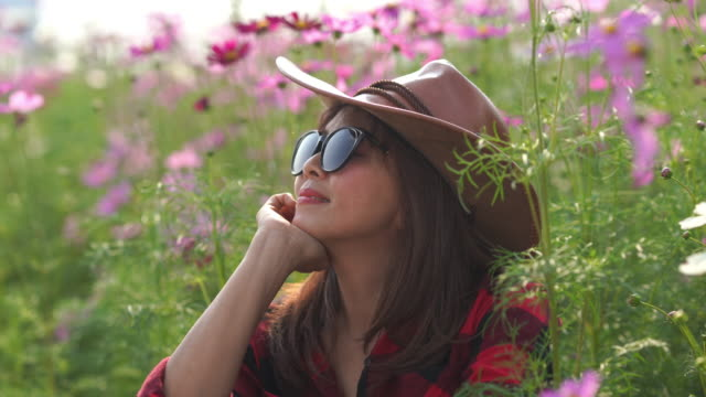 facial expression by Asian mature woman in cosmos meadow , relaxation with alternative lifestyle , retirement
