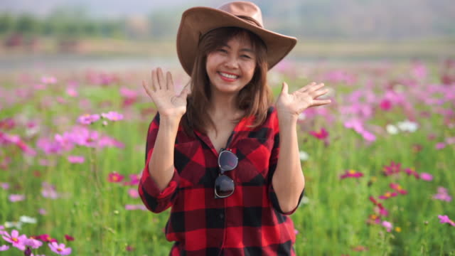facial expression by Asian mature woman in cosmos meadow , relaxation with alternative lifestyle , retirement , hello and goodbye gesturing