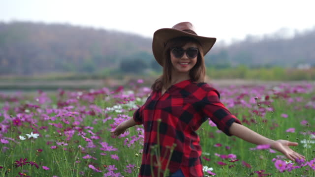 facial expression by Asian mature woman in cosmos meadow , welcome sign