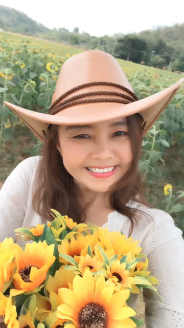 vídeos de stock e filmes b-roll de facial expression by asian mature woman in sunflowers field , vertical video for smart phone - vertical