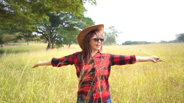 espressione facciale da donna matura asiatica in campo di grano, sentire la libertà con le braccia tese - braccio umano video stock e b–roll
