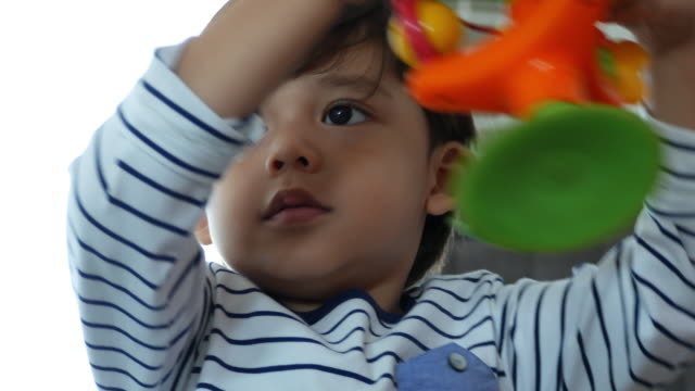 Facial expression by Caucasian ethnicity little boy playing toy - vídeo