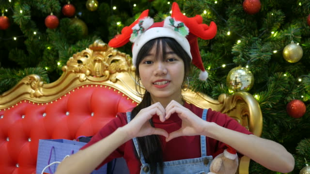 facial expression , heart sign by young woman in Christmas time video