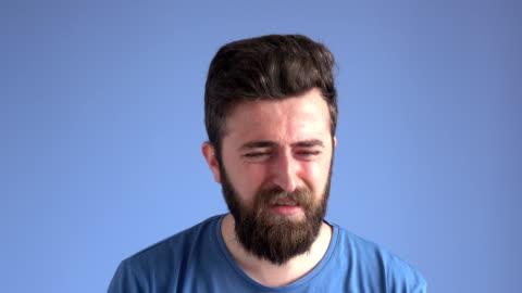 espressione facciale dell'uomo adulto piangente su sfondo blu - capelli castani video stock e b–roll