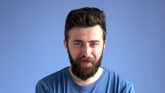 Facial Expression Of Flirting Adult Man On Blue Background 4K video of facial expression of flirting young man smiling on blue background. The model is an adult man in his 20's. He is wearing a blue shirt and he has brown hair and facial hair. He is making faces as he is flirting. background color stock videos & royalty-free footage
