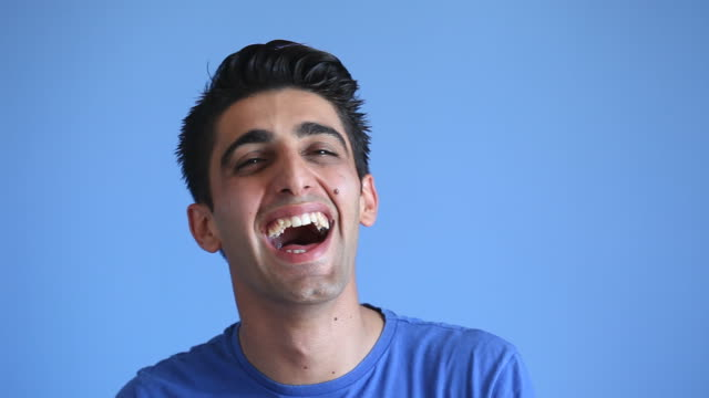 Facial Expression Of Laughing Adult Man On Blue Background video